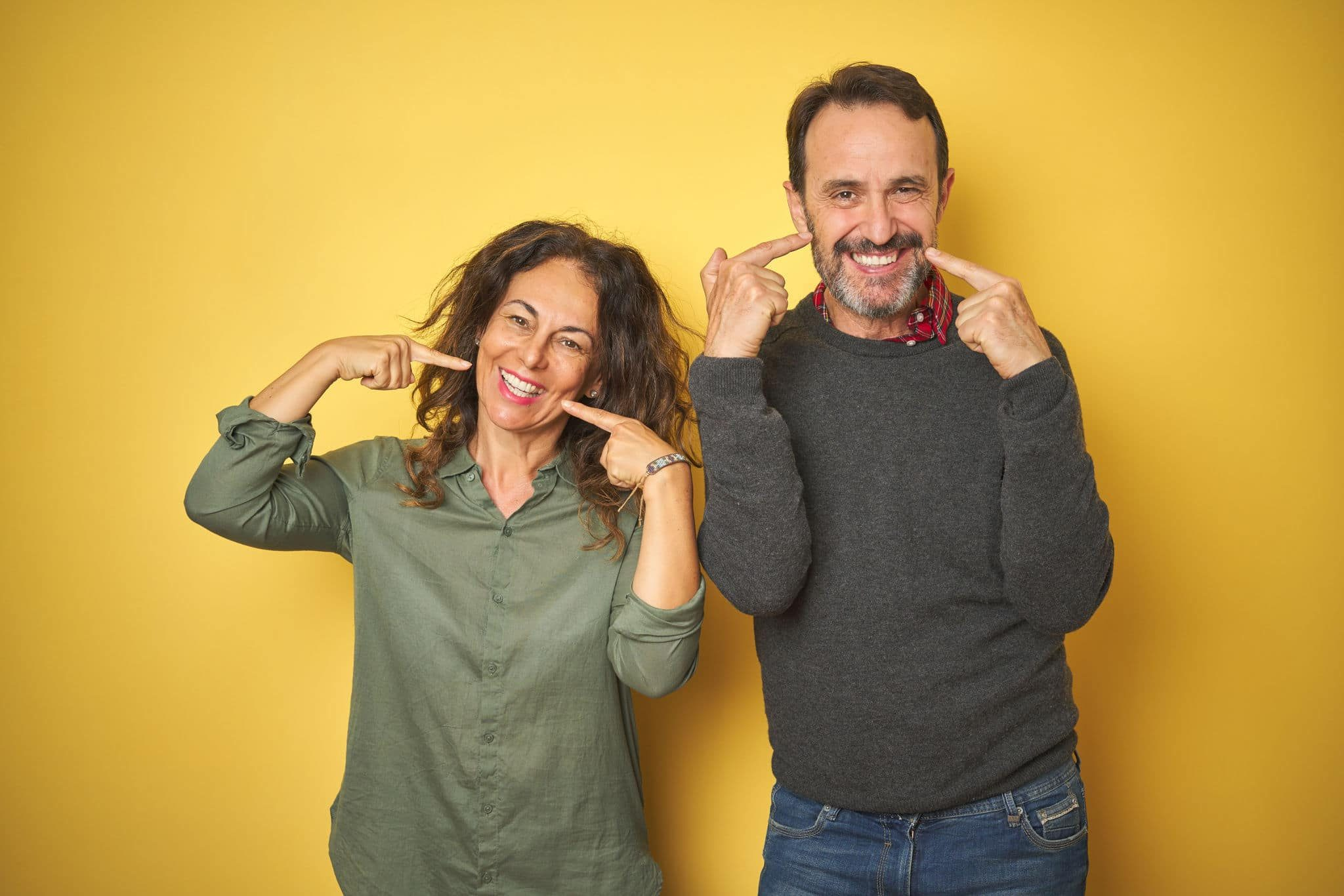 Beautiful middle age couple over isolated yellow background smiling cheerful showing and pointing with fingers teeth and mouth. Dental health concept.